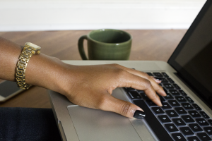 a black woman types on a laptop