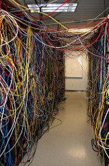 A server room full of very messy wiring. There are so many cables connecting devices together that you can't see the devices themselves,