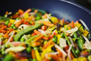 a frying pan full of brightly coloured vegetables cut into small pieces